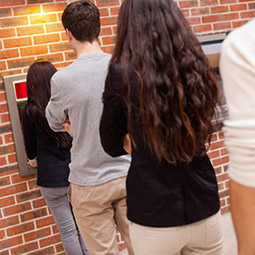 Image of a line of people waiting at an ATM