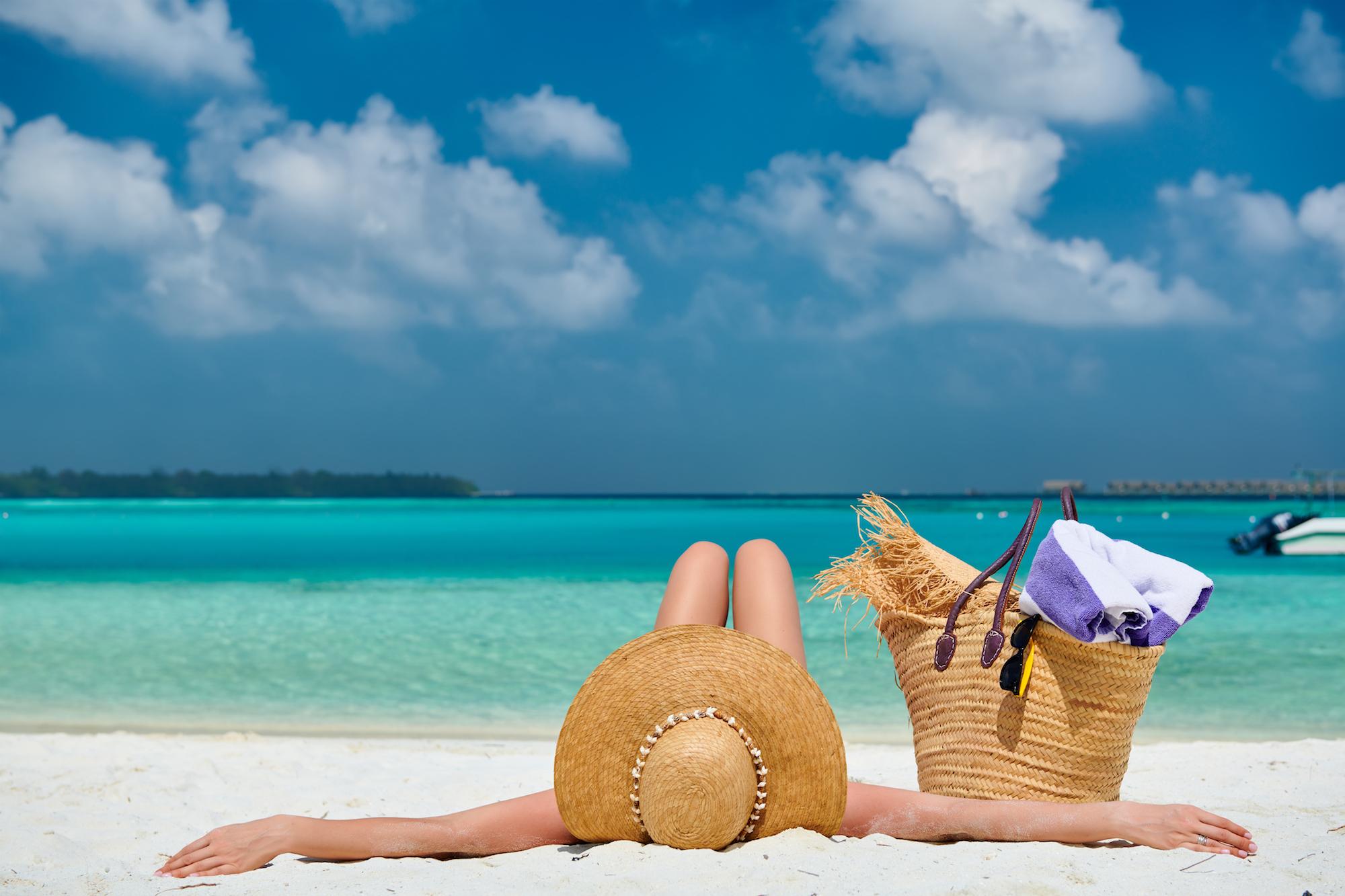 Woman lying down on beach. Summer vacation at Maldives