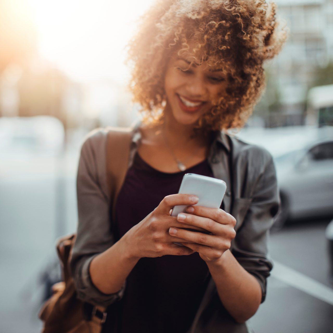 Female woman girl laughing and holding her phone outside
