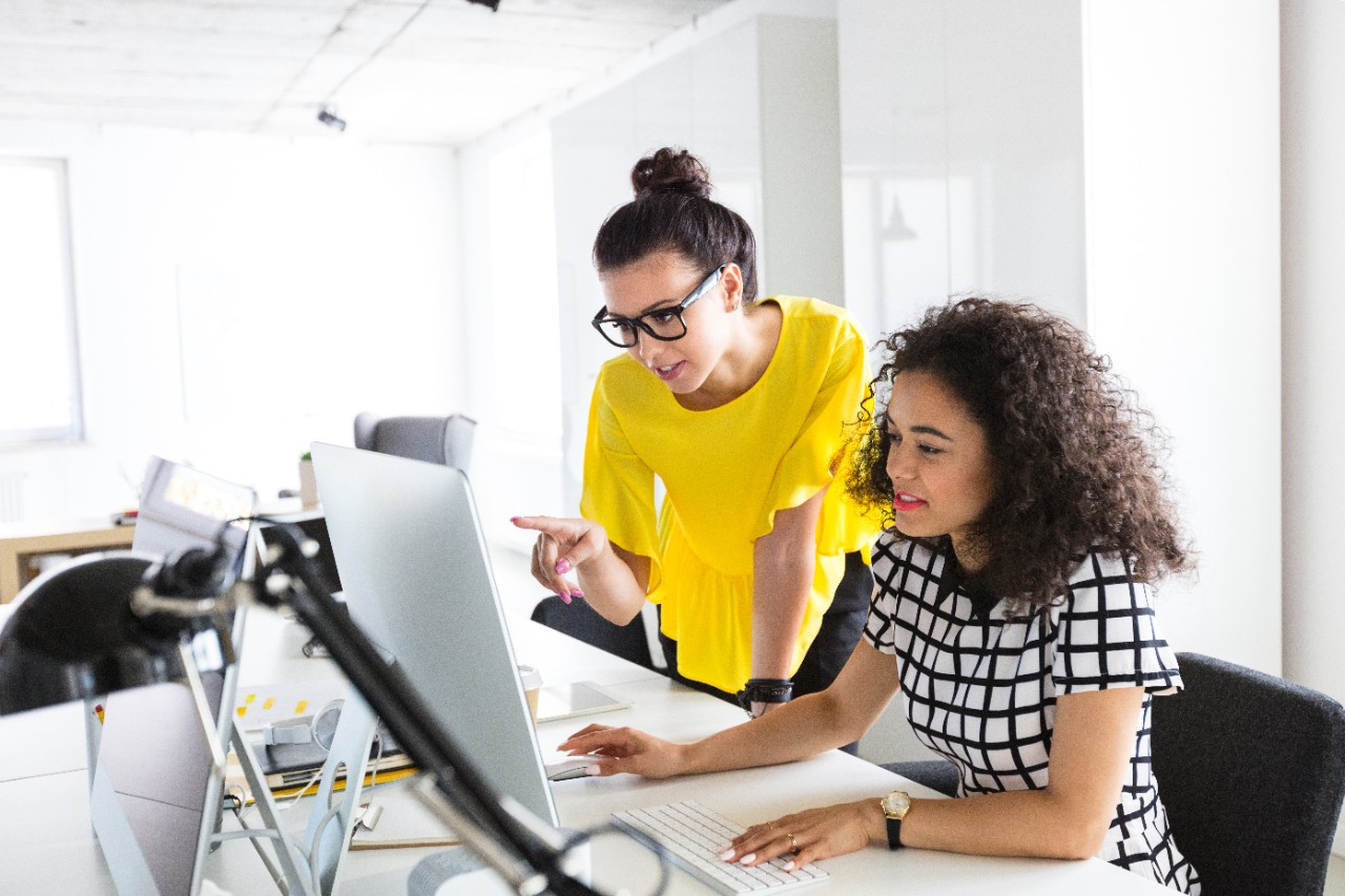 Two young businesswomen working together in the office at a desk. Female working on computer with colleague pointing at monitor.