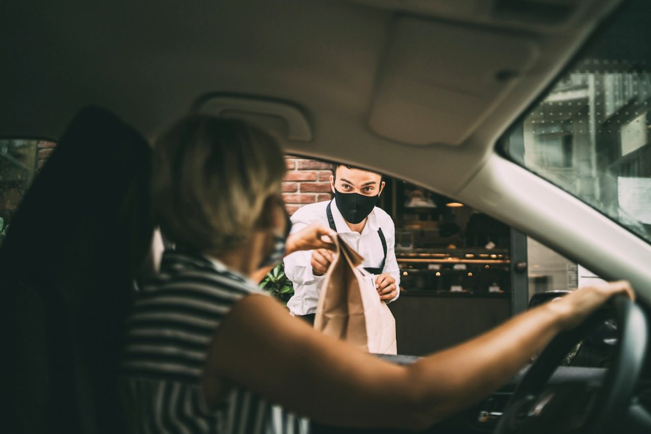 Waiter giving disposable package with food  to pretty smiling female driver