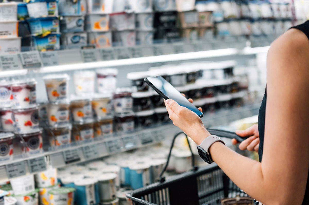 Cropped shot of young Asian woman holding shopping basket and checking her shopping list on smartphone while grocery shopping in a supermarket