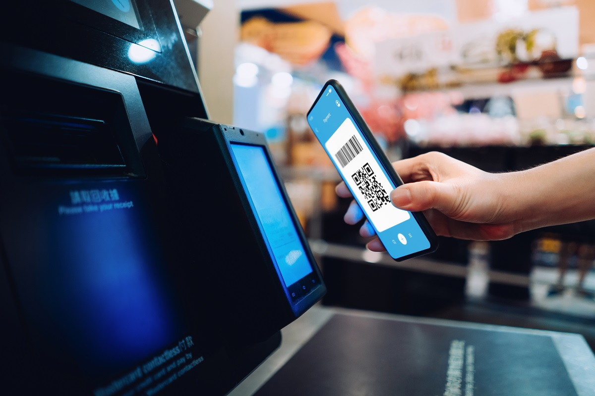 Close up of young woman shopping at a store, scanning QR code, making a quick and easy contactless payment via smartphone for her shopping at self-checkout kiosk. NFC technology, tap and go concept