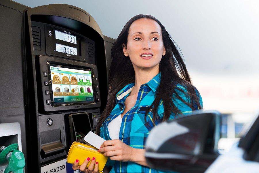 Young woman paying for the fuel at petrol station.
