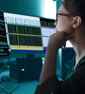 Stock photo of an Asian woman surrounded by computer monitors in a dark room