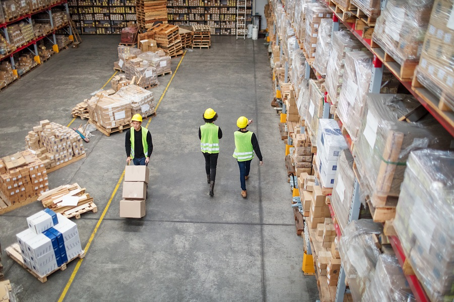 Workers working in large warehouse. Man moving boxed in a trolley with tow colleagues walking by in a distribution warehouse.