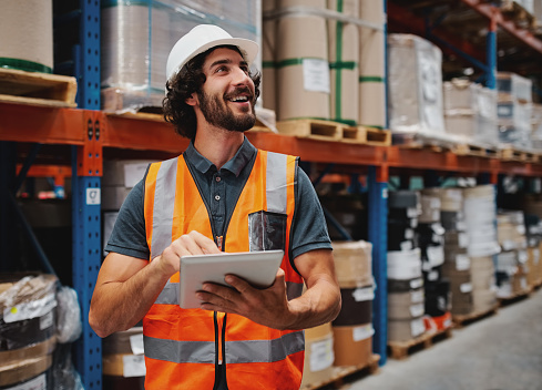 Portrait of young man wearing reflective jacket holding digital tablet standing in factory warehouse