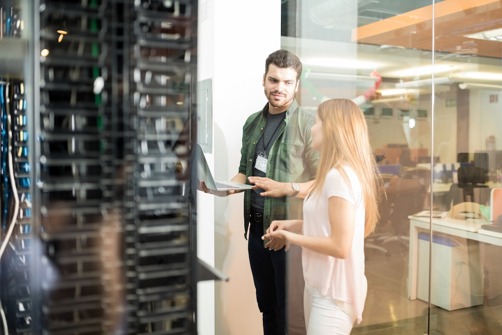 Two business people standing in server room with laptop and discussing