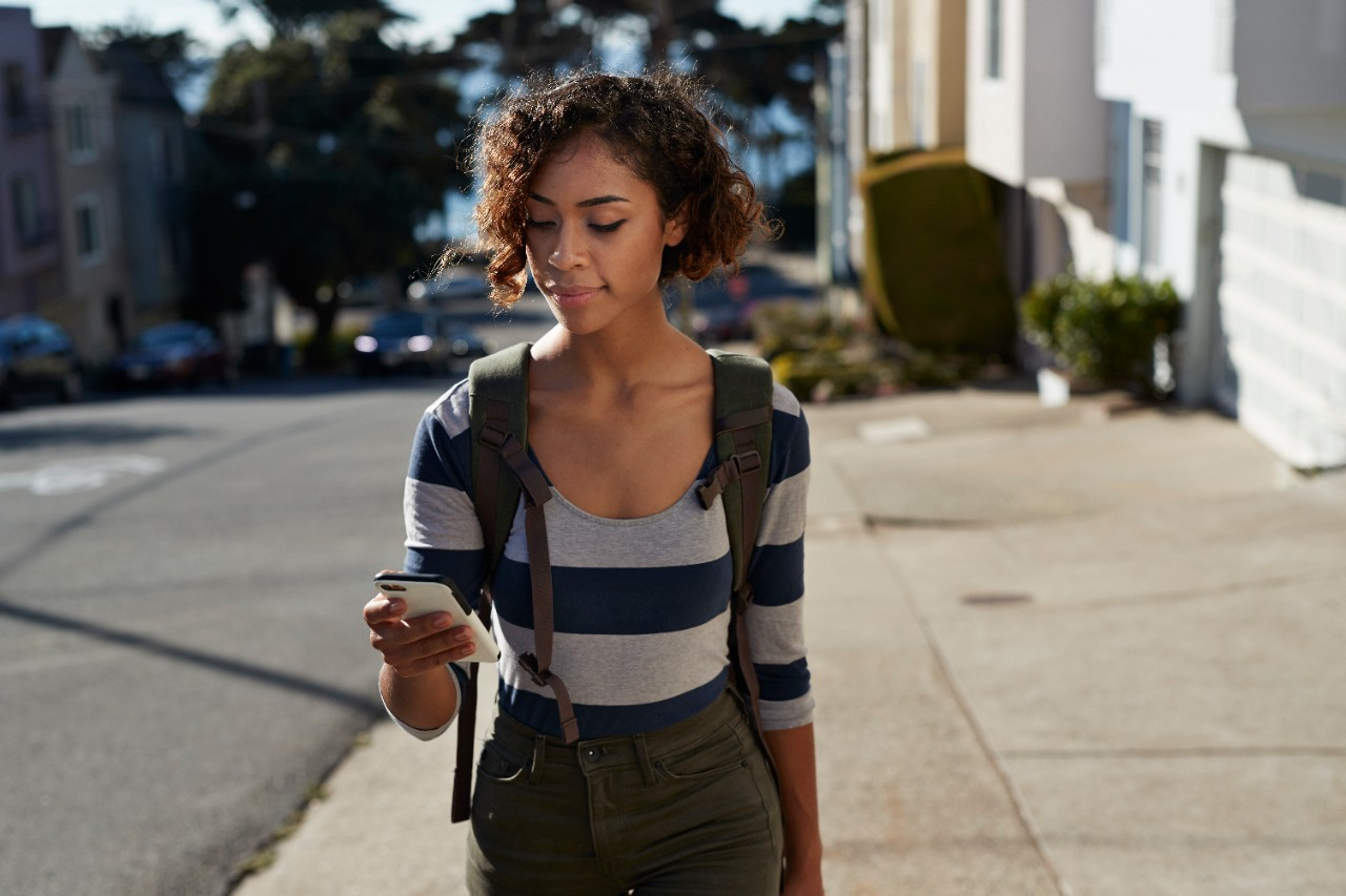 Young female girl woman looking on her phone smiling while walking down the street