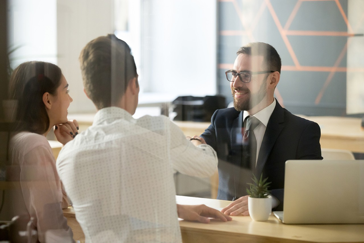 Smiling realtor or broker shaking hand of excited buyers couple, negotiating about first house purchase or taking loan, insurance agent welcoming clients with handshake at consultation meeting