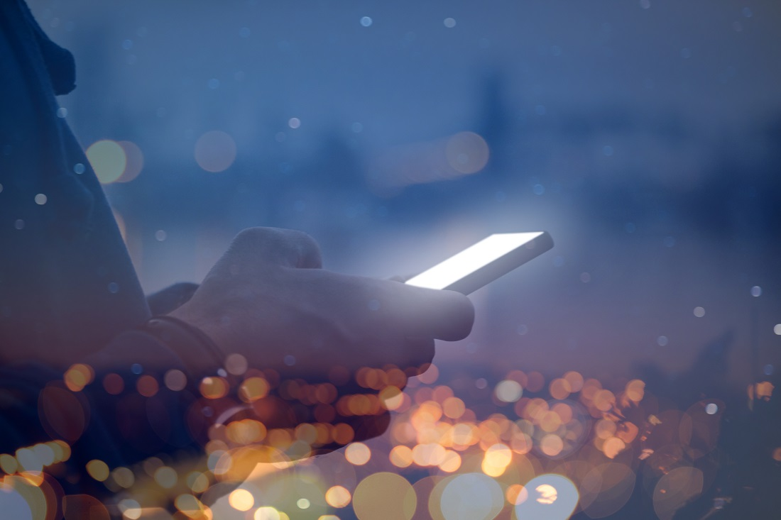 Person using modern smartphone at night with city streetlights in blurred background.