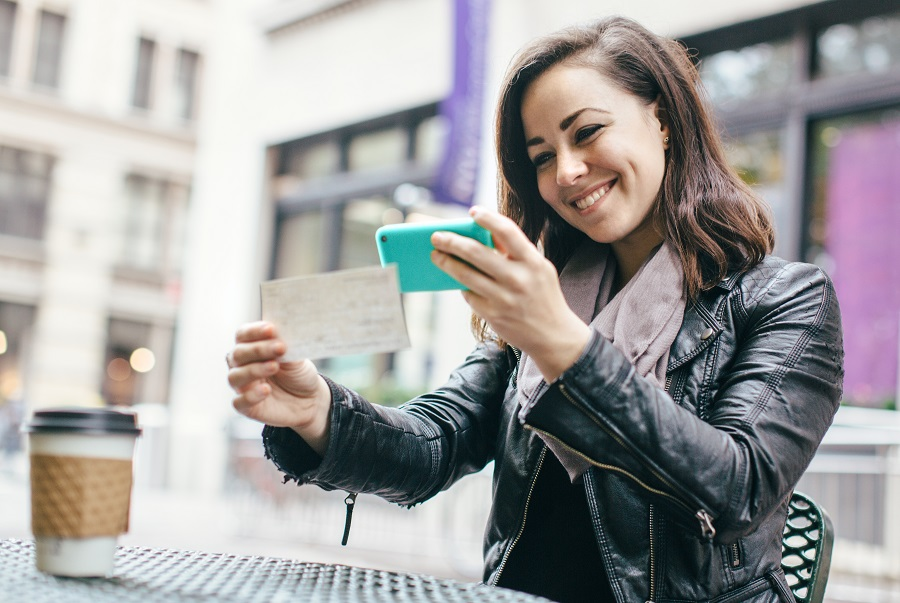 A beautiful Caucasian adult woman sits in a New York city park, taking a picture of a check with her smart phone for a  Remote Deposit Capture.  She smiles, wearing modern stylish clothing with darker and black colors.