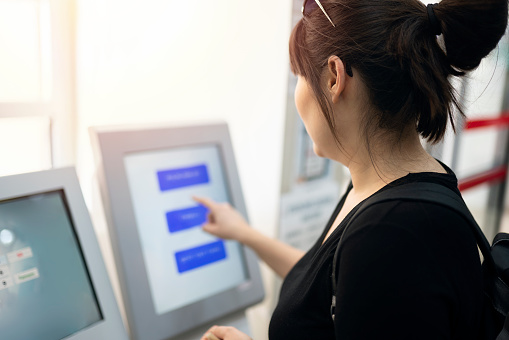 Young woman taking a number at a healthcare service center