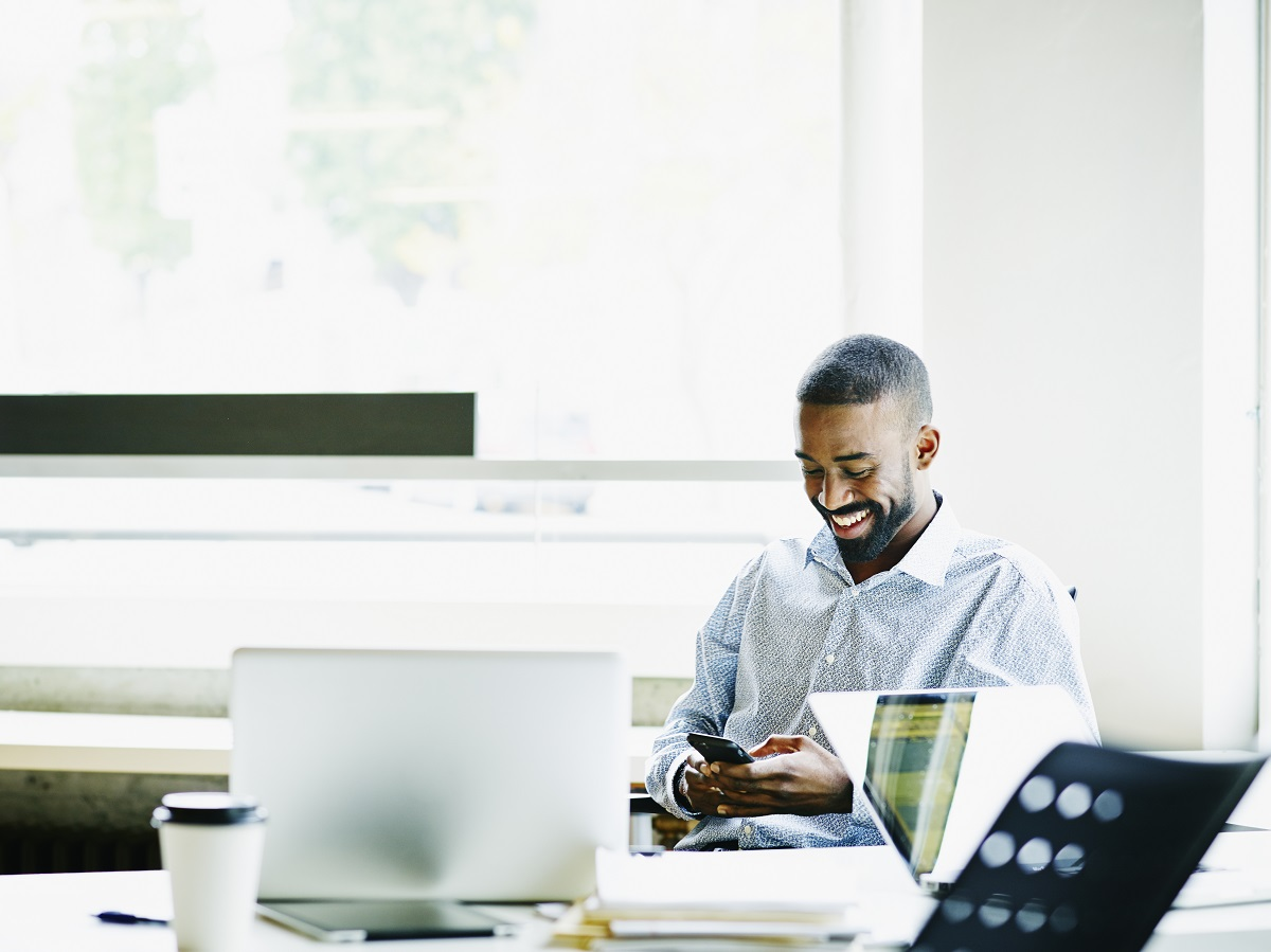 Smiling businessman sitting at workstation in office working on smartphone