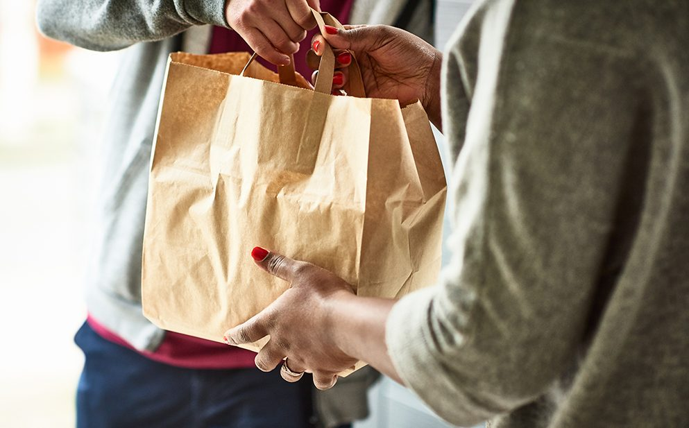 Woman holding paper bag with take out food, home delivery, food order, takeaway