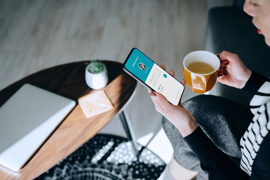 Young Asian woman relaxing at home drinking a cup of tea, logging in to her smartphone device. Lifestyle business, privacy protection, internet and mobile security concept