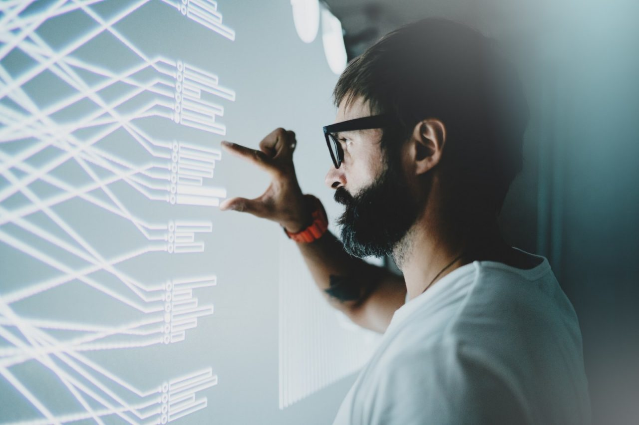 Concept of virtual panel display,diagram,digital graph interfaces.Attractive coworker touching virtual panel with graphs.Blurred background. Horizontal