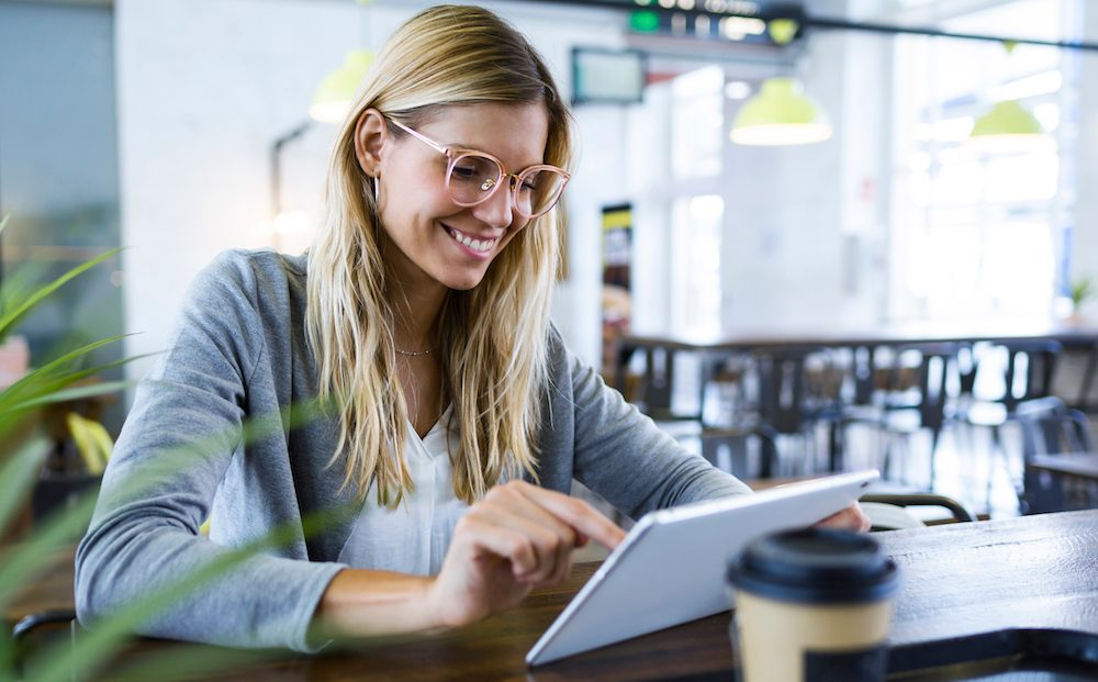 Young woman using her digital tablet while drinking coffee in the coffee shop