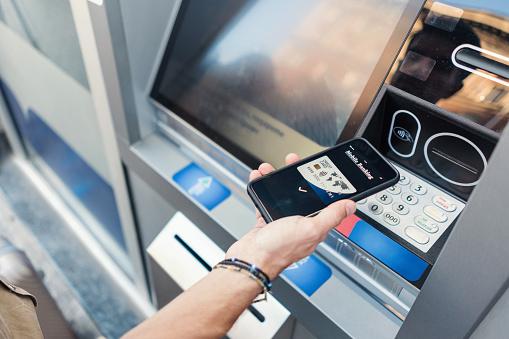 Close-up image of man making e-payments with his phone at the ATM device