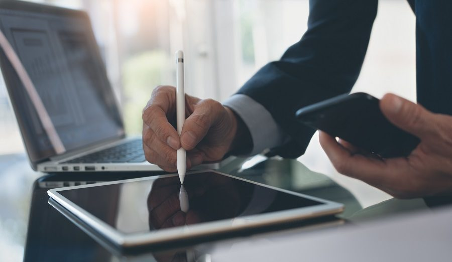 Electronic signature, Business and  technology concept. Businessman working on digital tablet signing business contract with digital pen, holding mobile smart phone with laptop computer and business document on office desk, close up