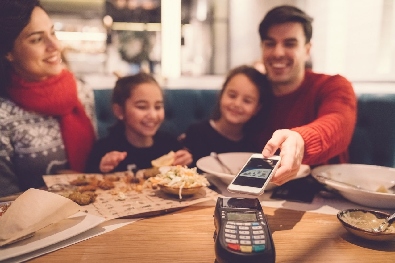 Family with two kids eating dinner in restaurant and paying with smartphone