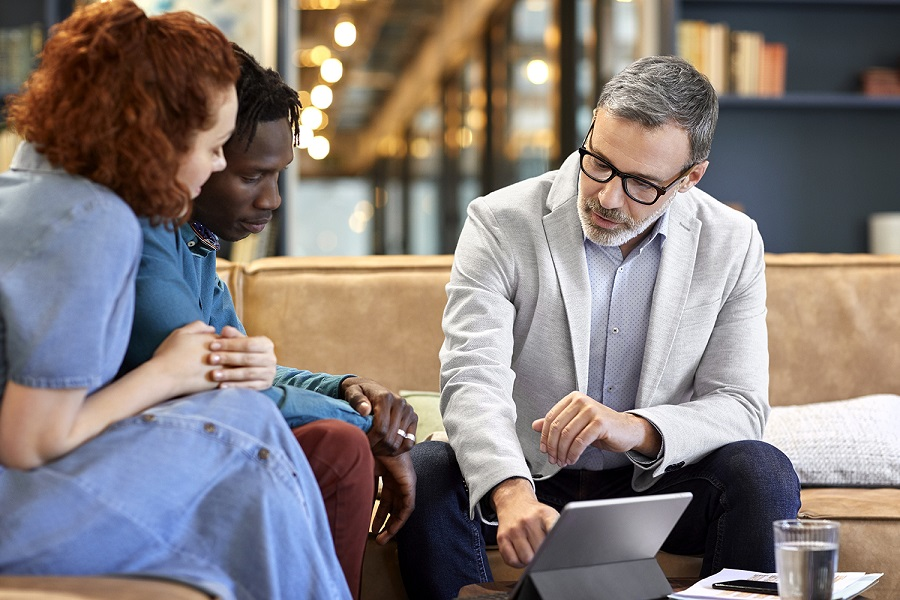 Mature financial advisor planning with young multi-ethnic couple at office. Businessman is discussing over digital tablet with clients at workplace. They are sitting in meeting.