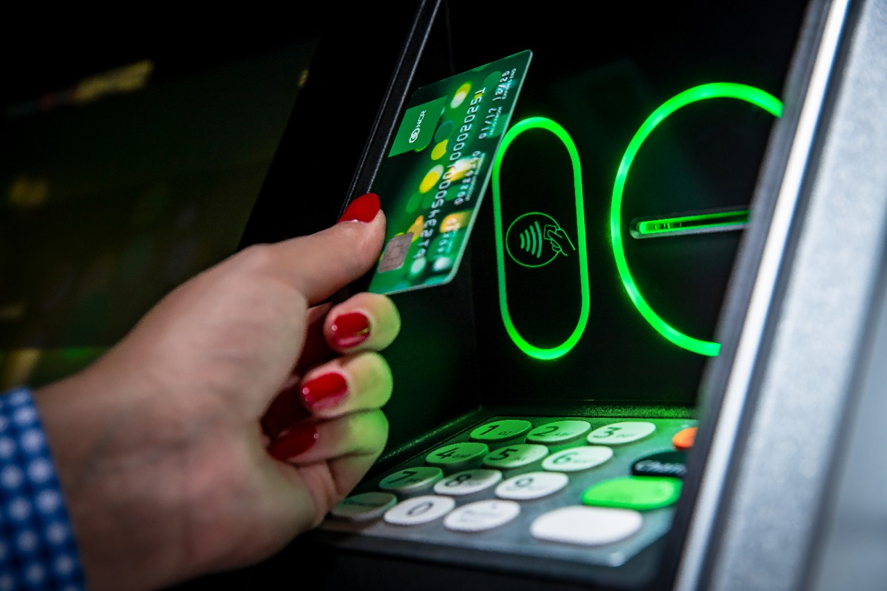 NCR ATM with woman putting card into slot over keypad