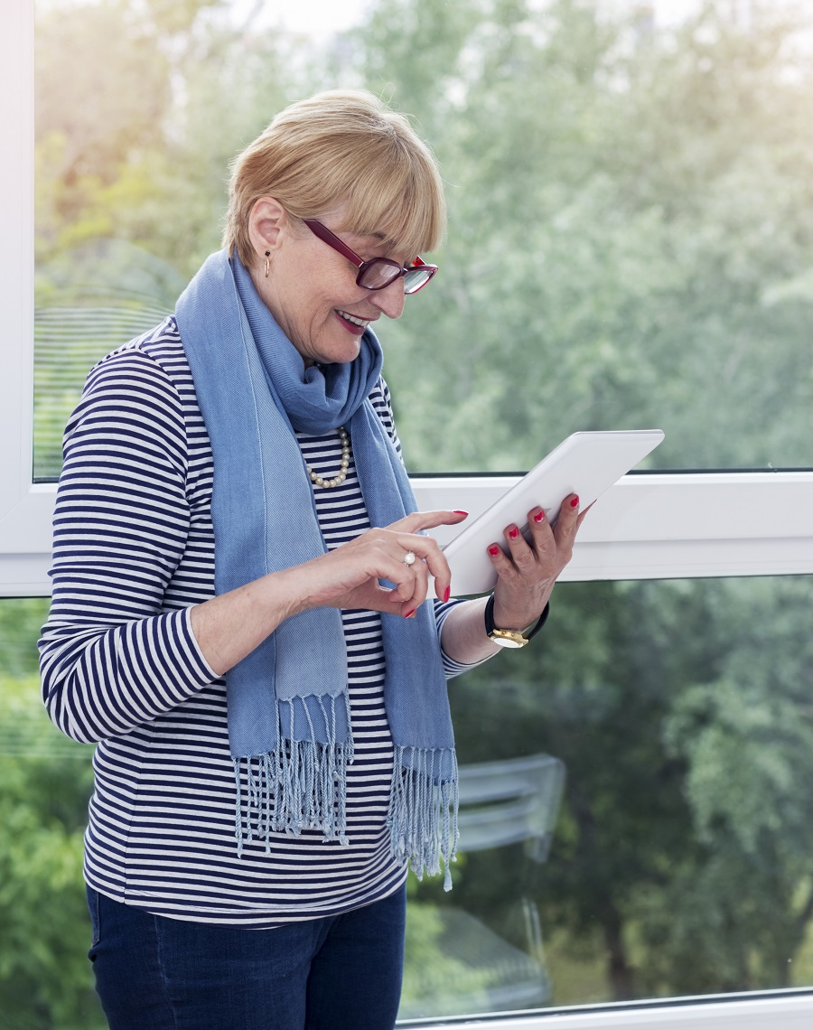 Charming senior woman  standing next to the window and using a touchpad.