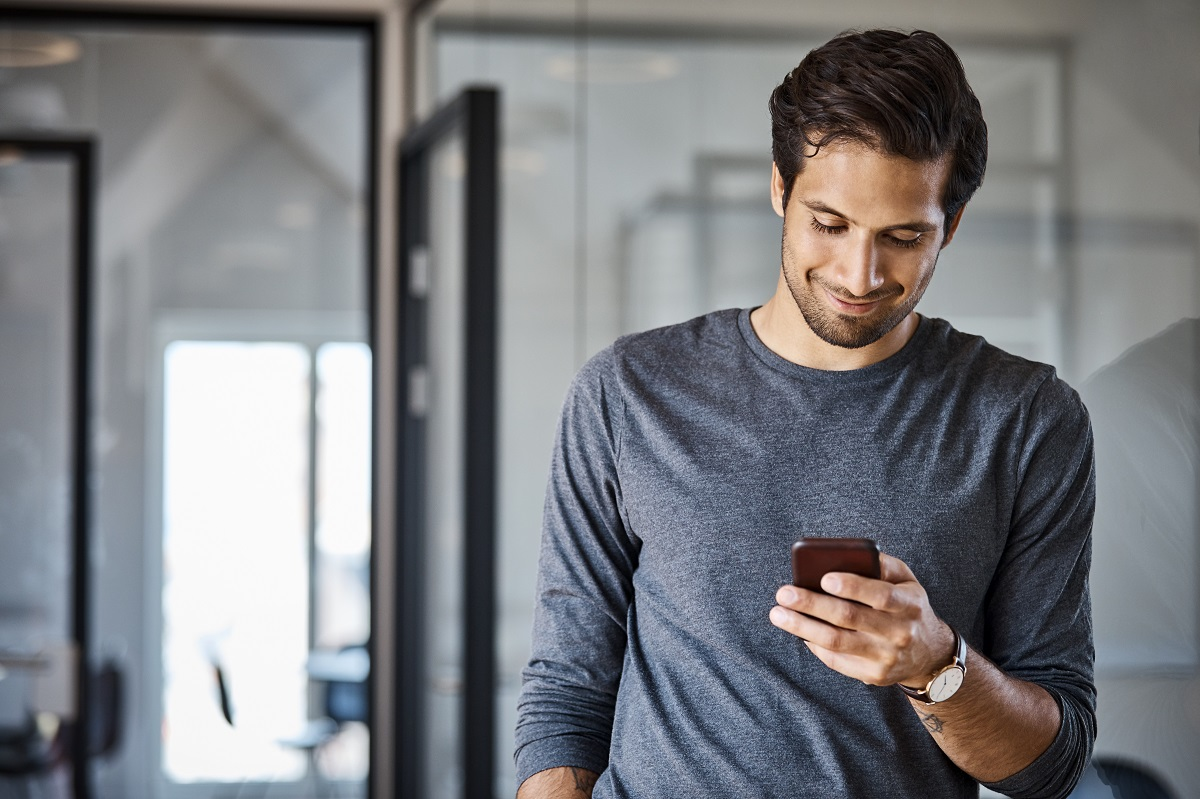 Young male professional using mobile phone at office