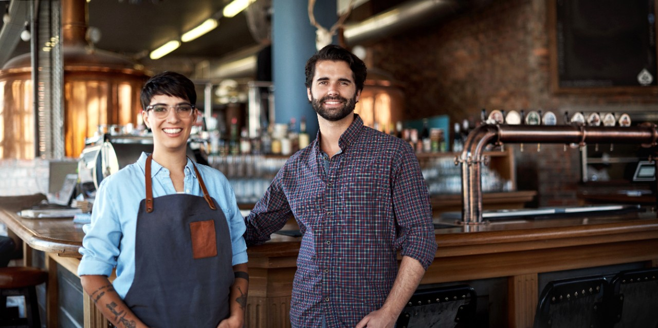Portrait of two young business owners in their bar