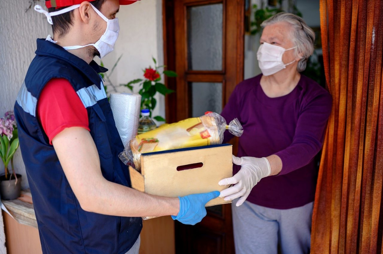 Delivering food ordered online while in home isolation during quarantine. Courier in protective mask delivers parcel to client.