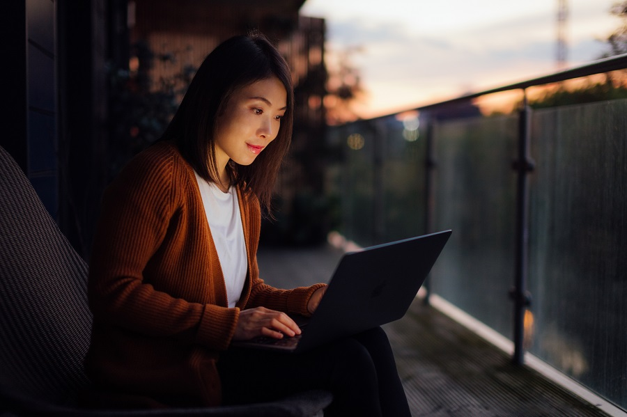 Beautiful young Asian woman working with computer on her lap, sitting on the balcony at night.
