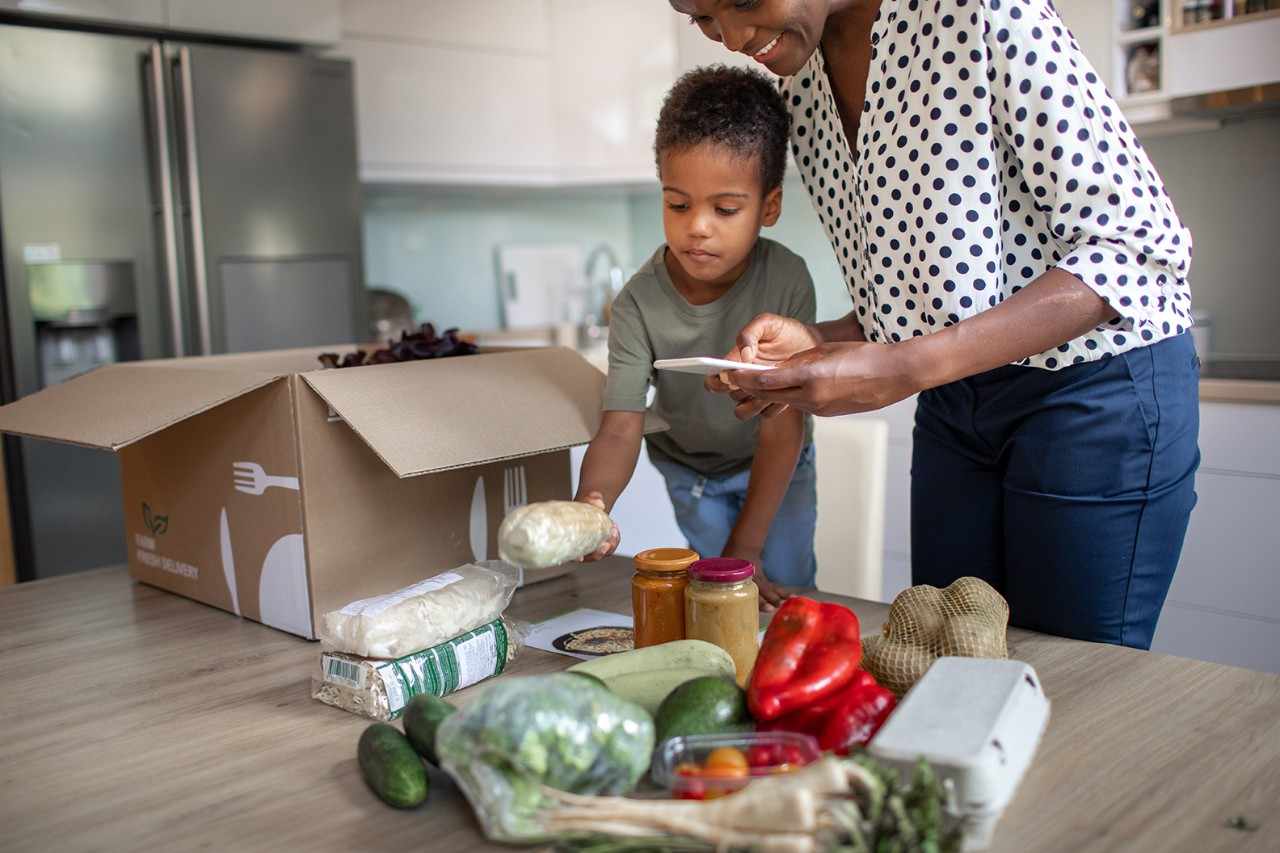 Mother and her son opening parcel with meal kit in their kitchen. Woman photographing groceries.