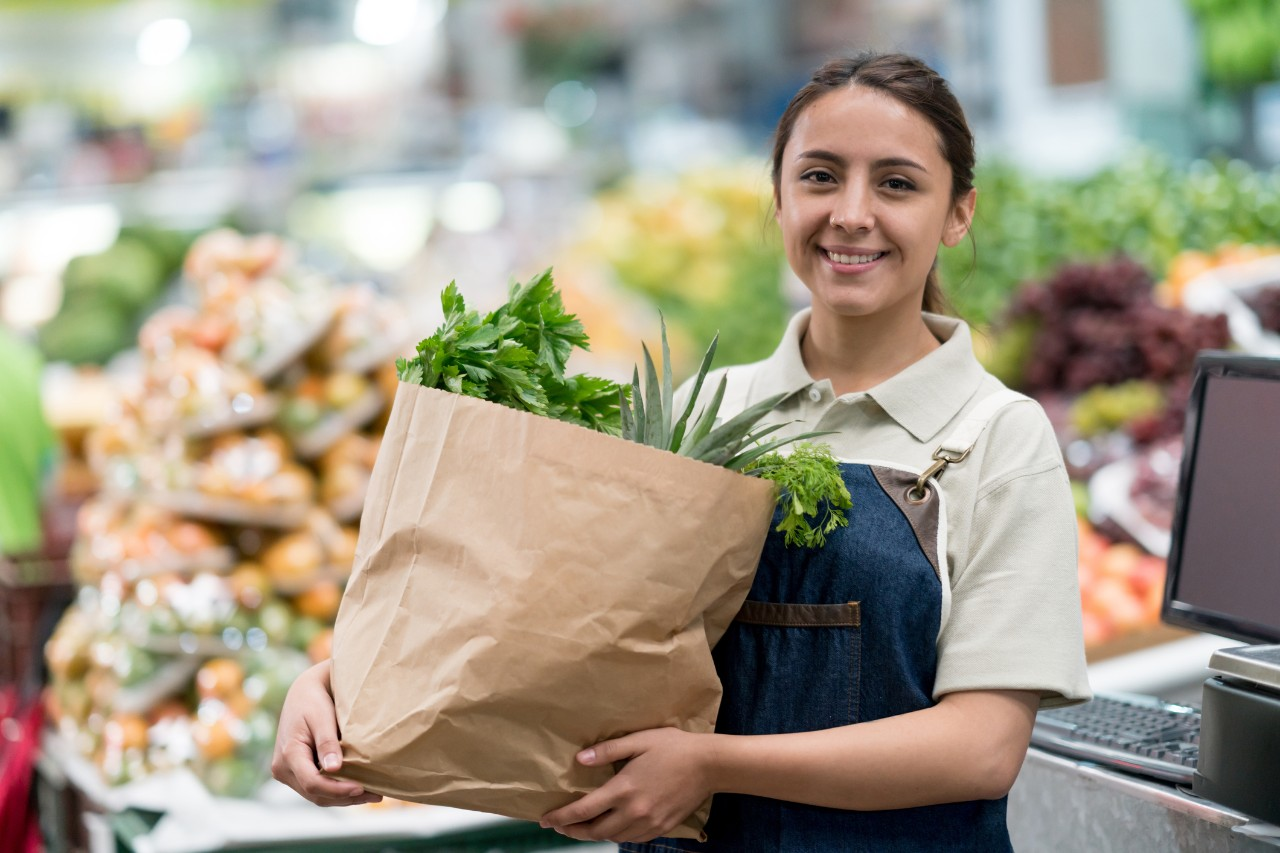 Portrait of a woman working at a supermarket and carrying a bag of groceries while looking at the camera smiling