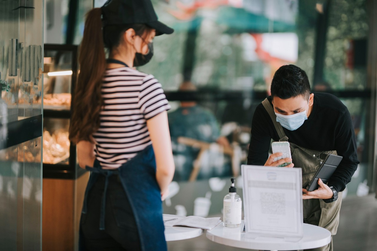 asian chinese cafe waitress checking body temperature for client as standard procedure and check in process before entering cafe as new normal