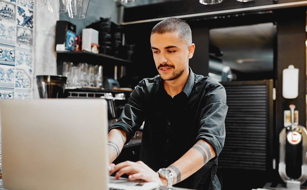 shot of a male restaurant owner using a lapatop inside of his cafe