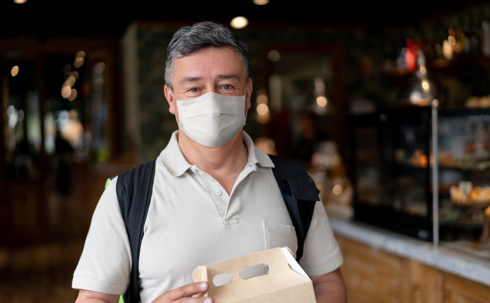 Delivery man picking up food at a restaurant wearing a facemask during the COVID-19 pandemic and looking at the camera