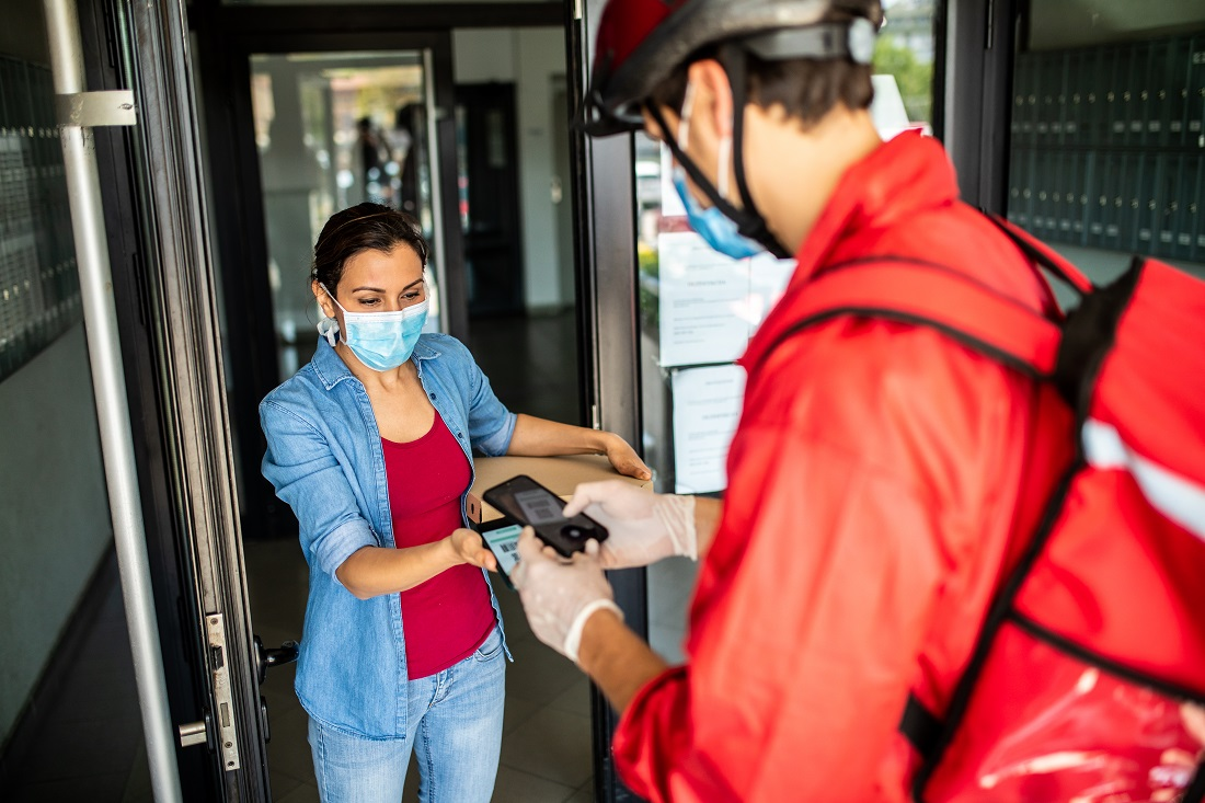 Pizza delivery person wearing red jacket, cycling helmet, protective face mask and surgical gloves, scanning bar code on customers smart phone and making a quick and easy contactless payment