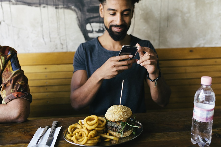 A man using his smartphone, taking photos of his burger before eating it at a trendy restaurant.