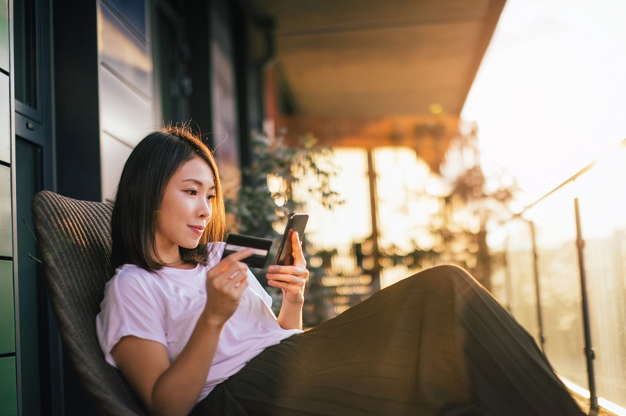 Smiling young Asian woman using smart phone and credit card to mange online banking, sitting on the balcony with dramatic sunlight. Online shopping makes life easier.