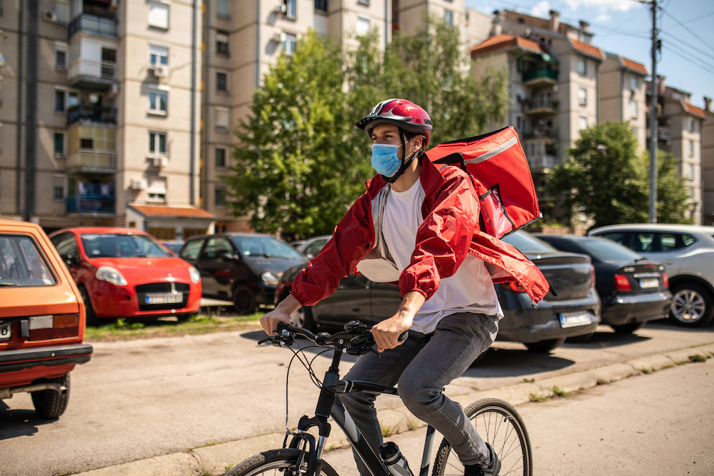 Delivery man wearing red jacket, cycling helmet, protective face mask and backpack riding bike to his next customer during coronavirus pandemic