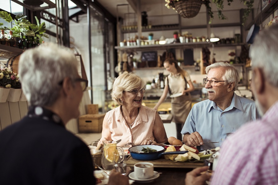 Close up of a group of seniors enjoying food in a restaurant
