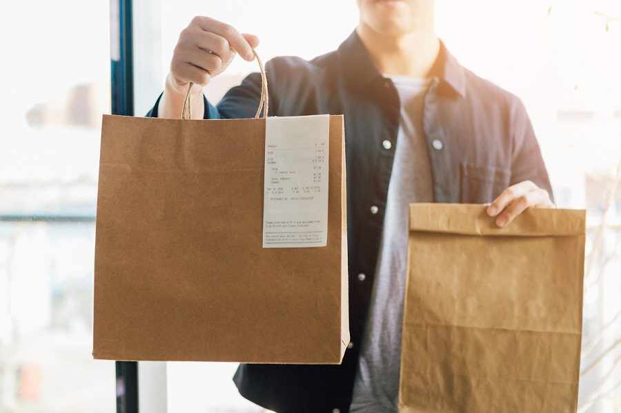 Close up shot of an unrecognisable man making food delivery, carrying takeaway paper bags.