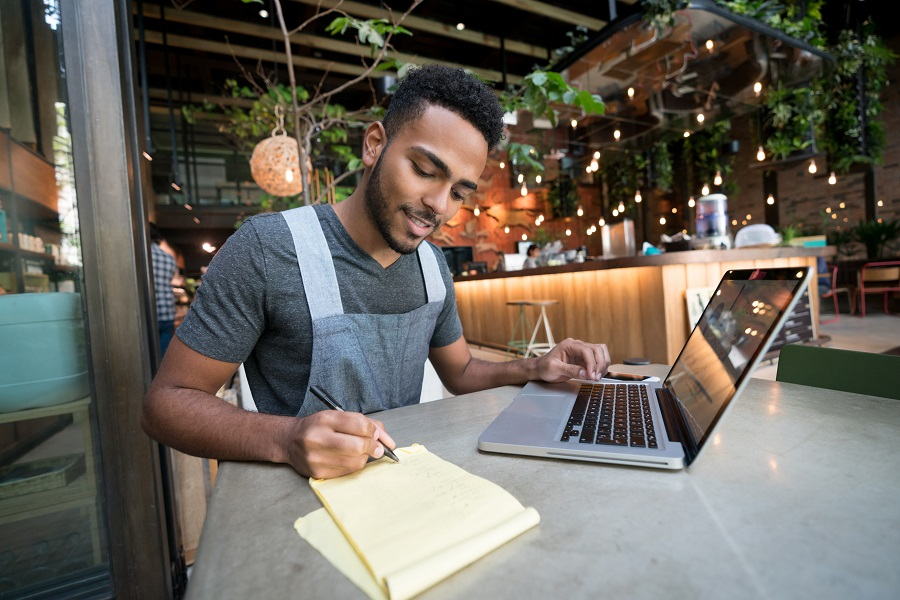 Happy man doing the books at a restaurant using a laptop computer - small business concepts