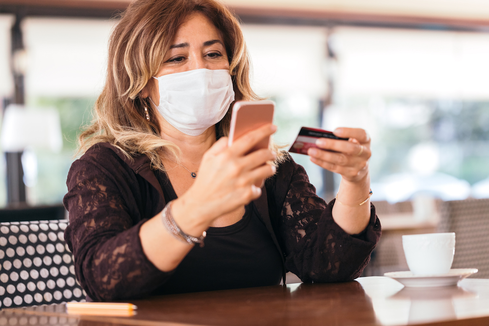 Woman wearing protective face mask and  shopping online in a cafe