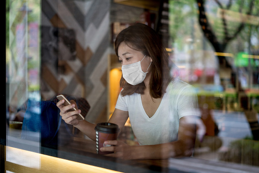 Asian woman at a cafe wearing a facemask and texting on her phone â COVID-19 lifestyle concepts