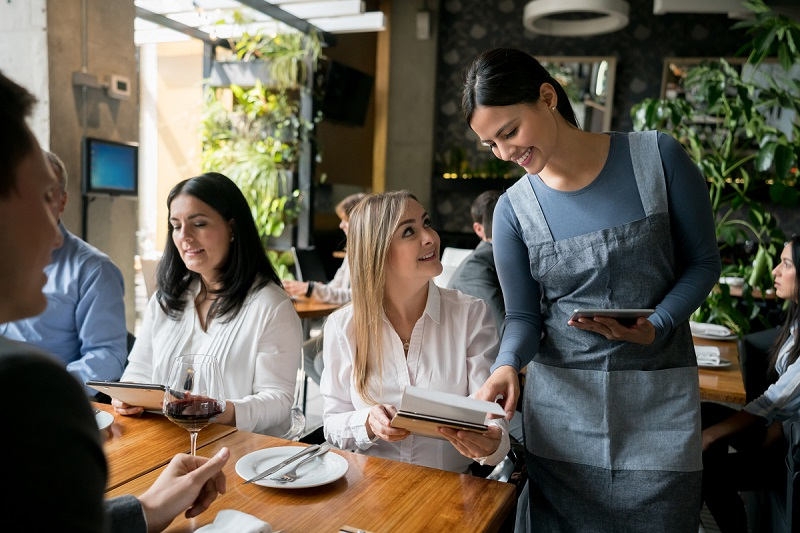 Waitress serving a group of people at a restaurant and helping woman with the menu - food service concepts