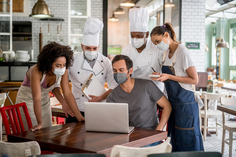 Staff meeting with the business owner of a restaurant wearing facemasks and preparing for reopening during the COVID-19 pandemic