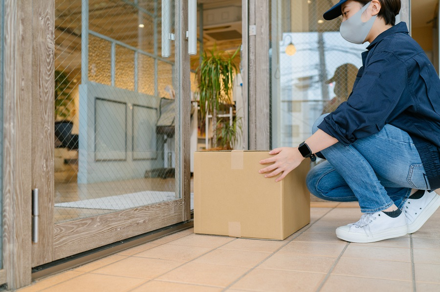 A delivery person is placing a parcel at the doorstep of a small shop.