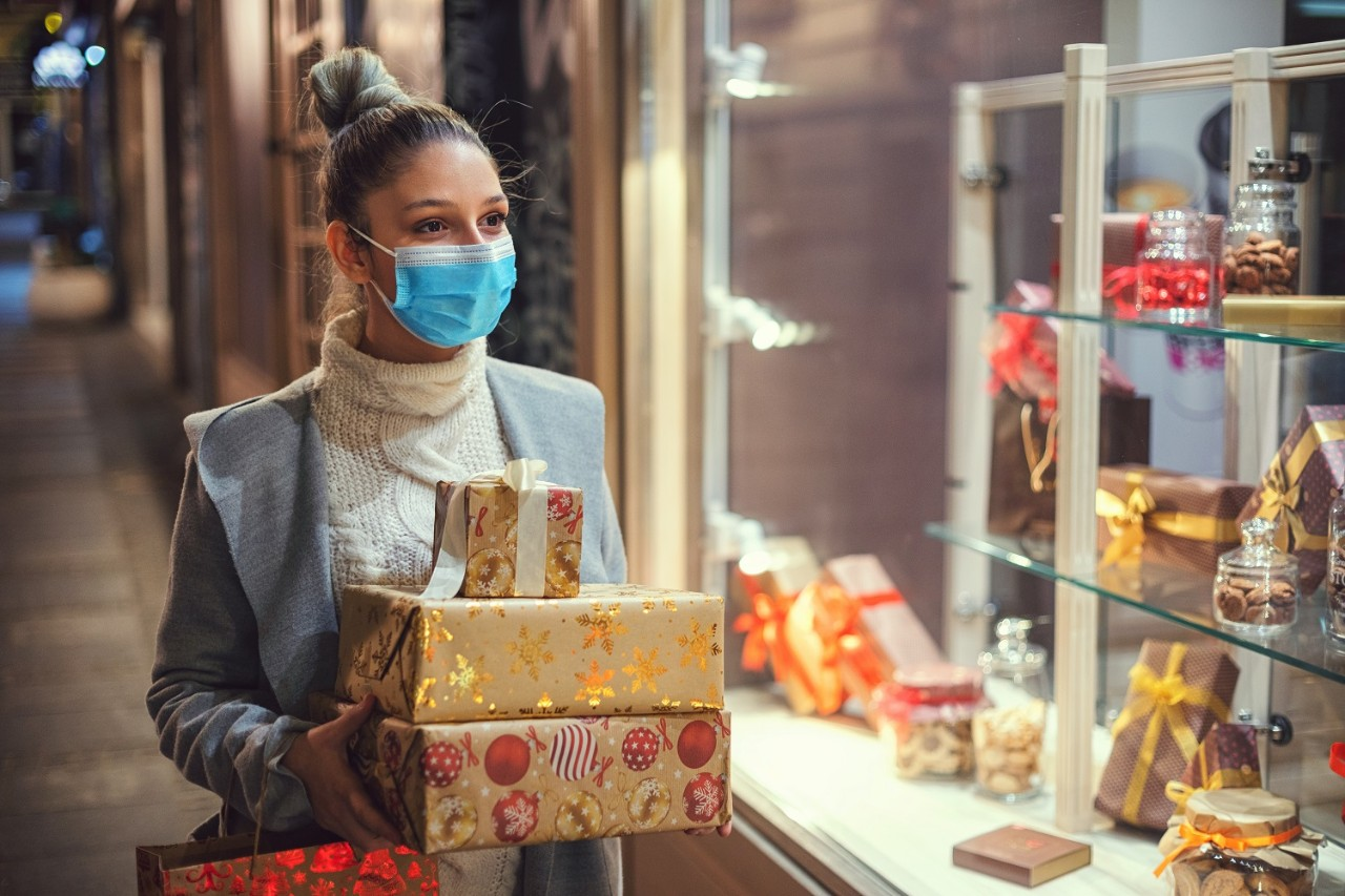 Teenage girl walking and shopping Christmas gifts in the city. She wears a protective mask to protect from corona virus COVID-19.